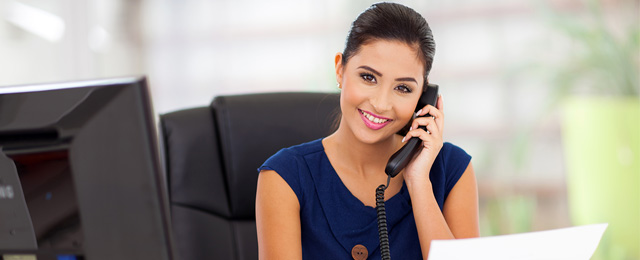 smiling woman at desk on phone